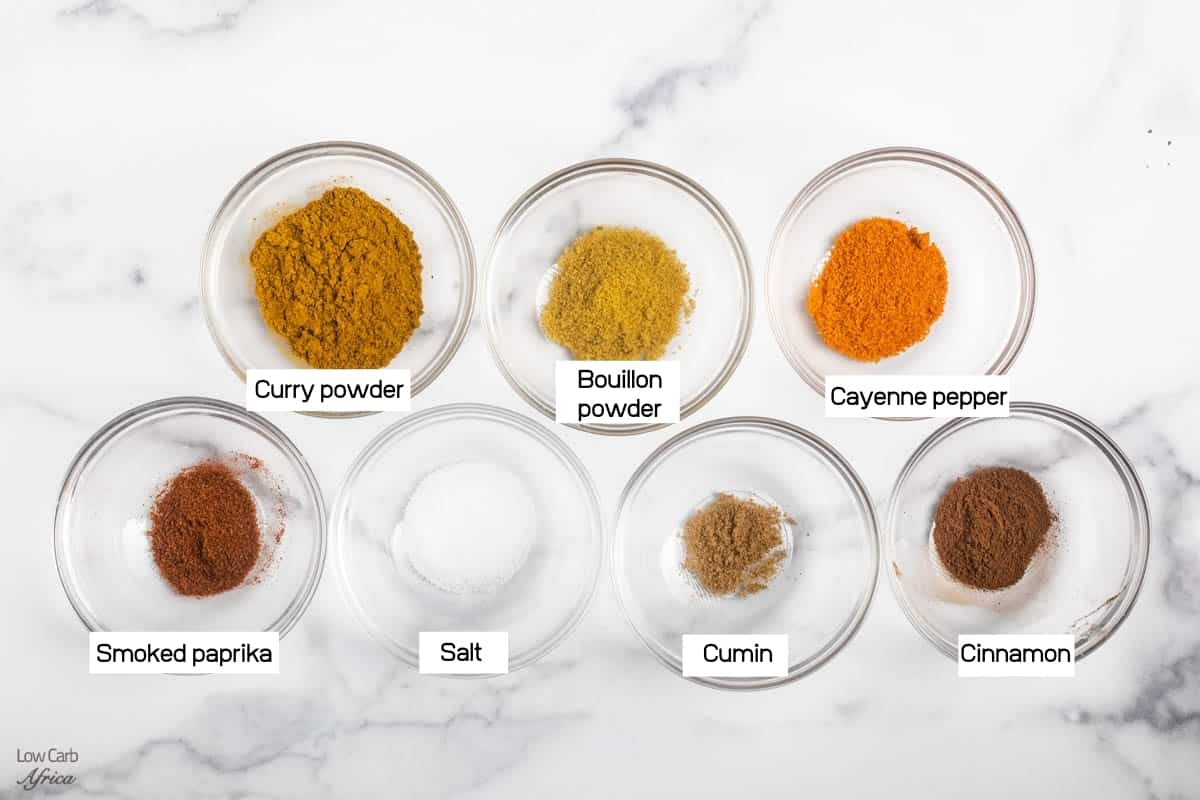 individual glass bowls of paprika, cumin, salt, cayenne pepper, cinnamon. on a white marble surface.