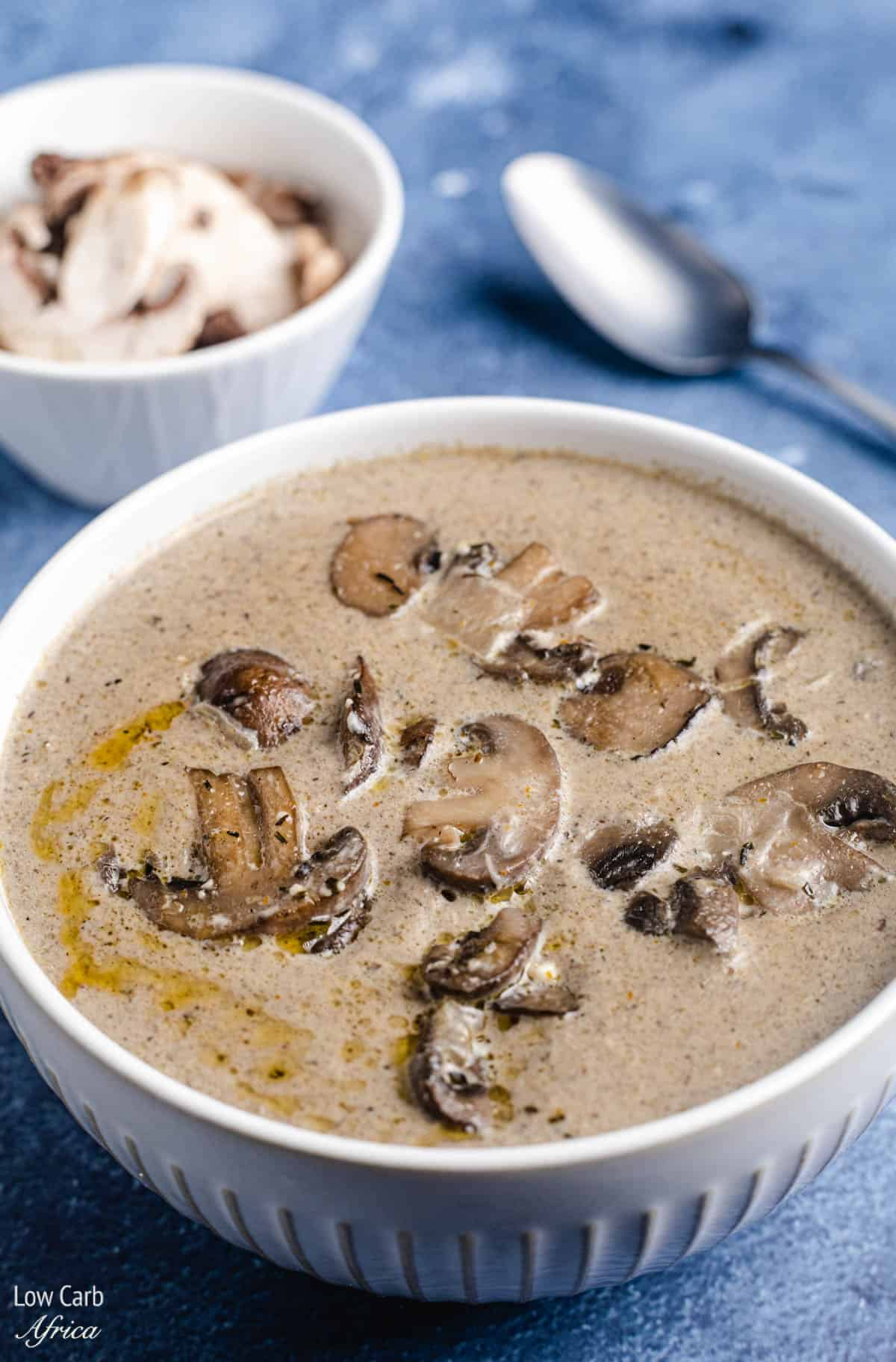 A bowl of keto mushroom soup with a spoon on the side