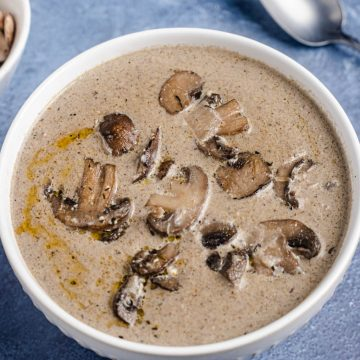 a wide image showing a bowl of soup with mushrooms on top