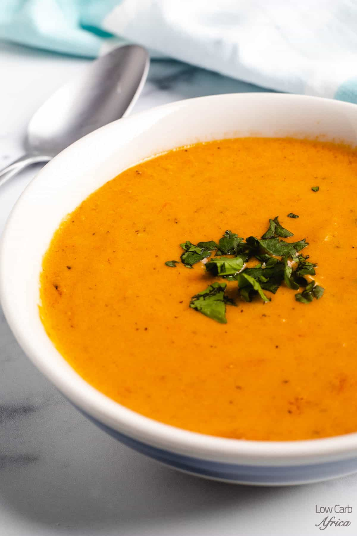 creamy keto tomato soup in a white bowl